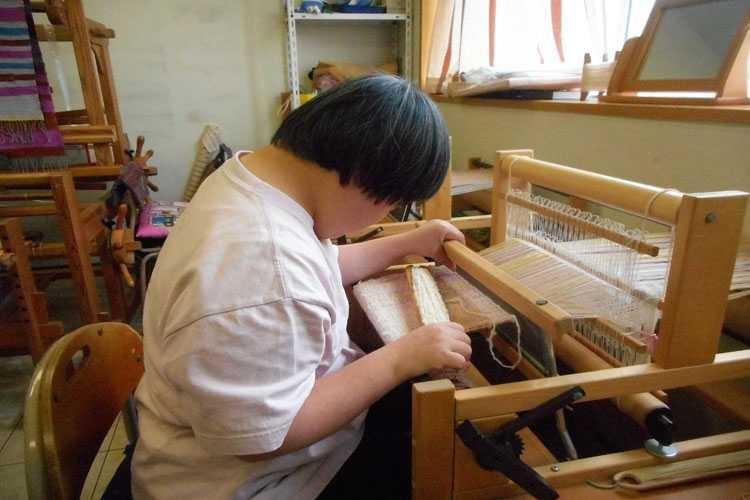 機織り作業をする利用者さんの写真