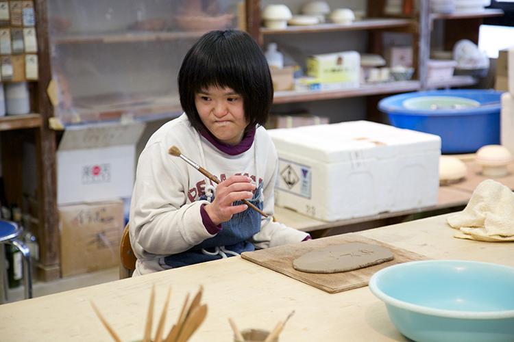 陶芸に絵入れをする利用者さん写真