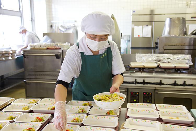 食堂で仕事中の女性達の写真