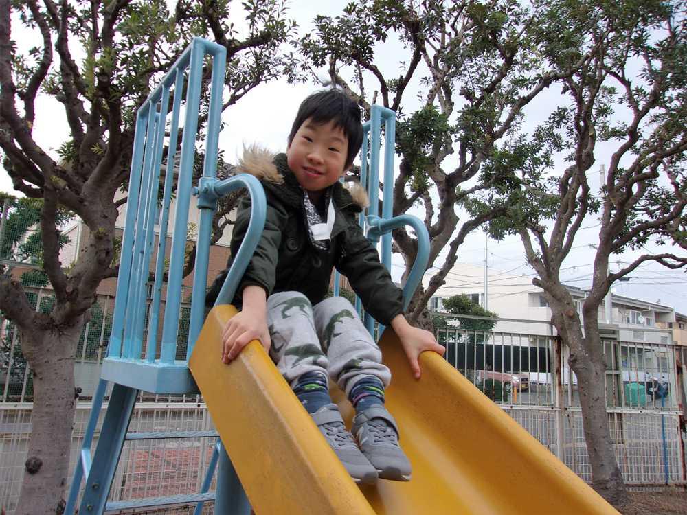 滑り台に乗って笑顔の児童
